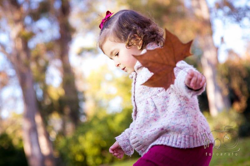 niña andando por el parque con lazo rojo en el pelo y hoja en la mano