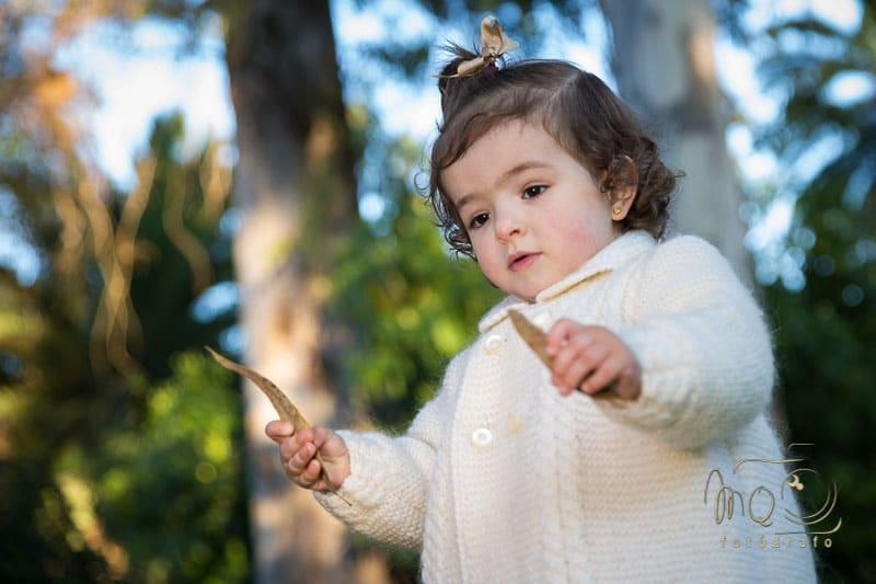 niña en el parque con rebeca blanca de punto