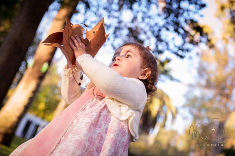 niña de lado con hojas en las manos