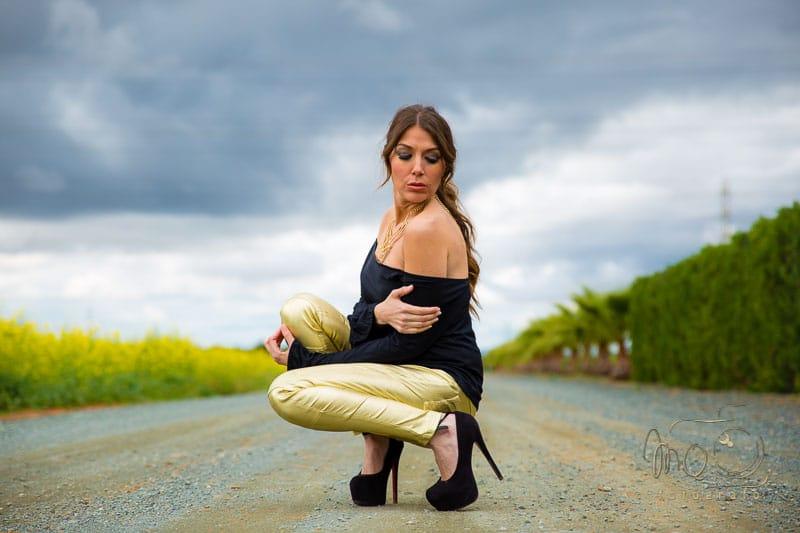 modelo agachada en camino con tacones y pantalón oro