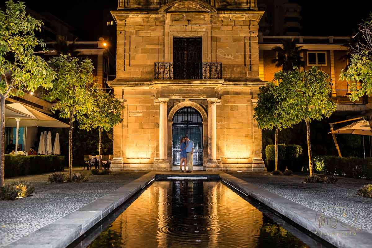 novios en la fachada de la capilla del muelle de málaga de noche