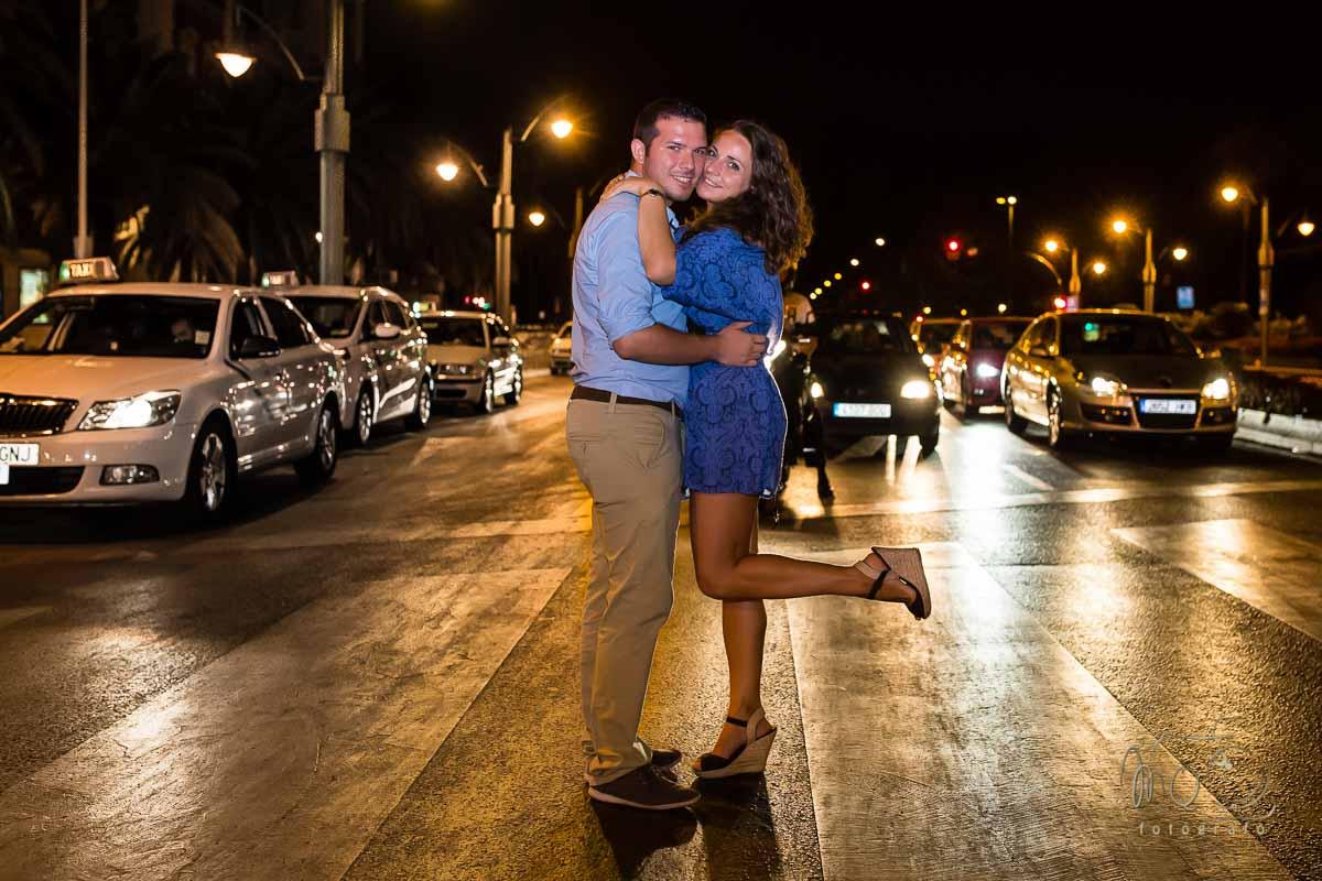 novios abrazados en su preboda, delante de los coches en un semáforo