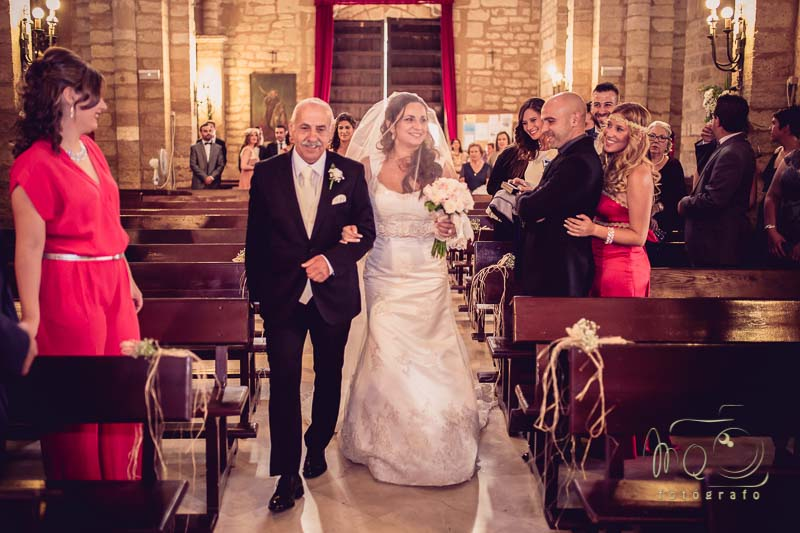 novia de la mano del padre por el pasillo de la iglesia