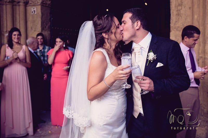 novios besándose después del arroz a la salida de la iglesia
