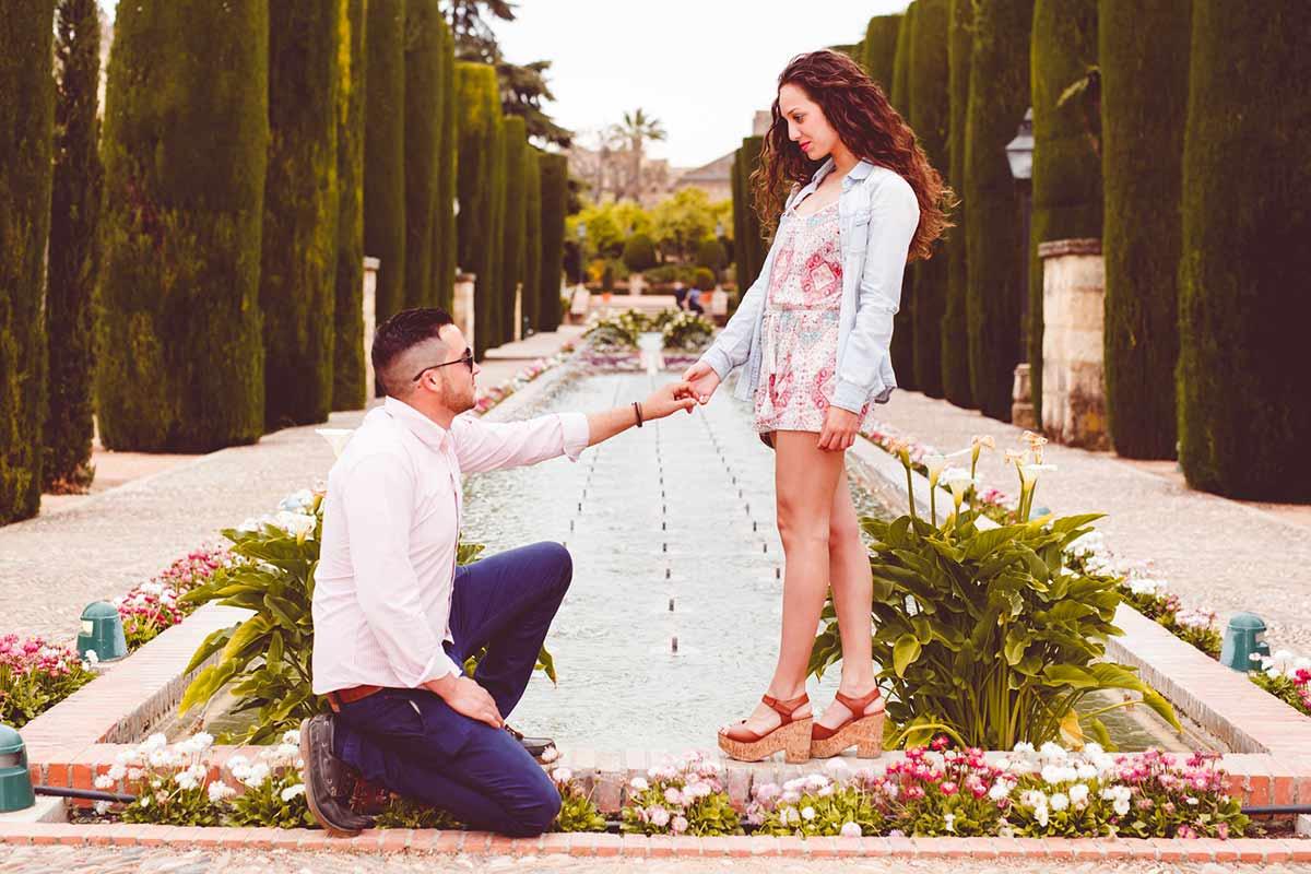 Mejor lugar para reportaje de boda en Córdoba novio arrodillado frente a novia cogiéndole la mano en junto al estanque del  alcázar