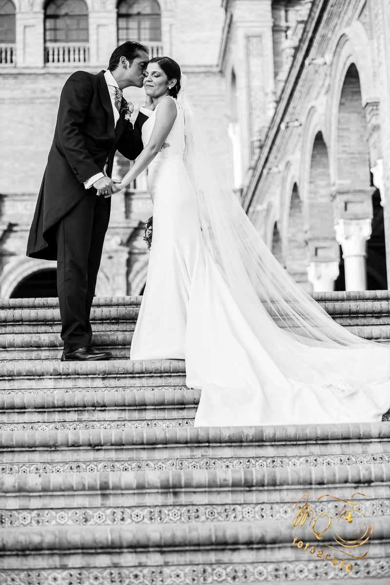 novio besando a la novia en las escaleras de la plaza de España Sevilla