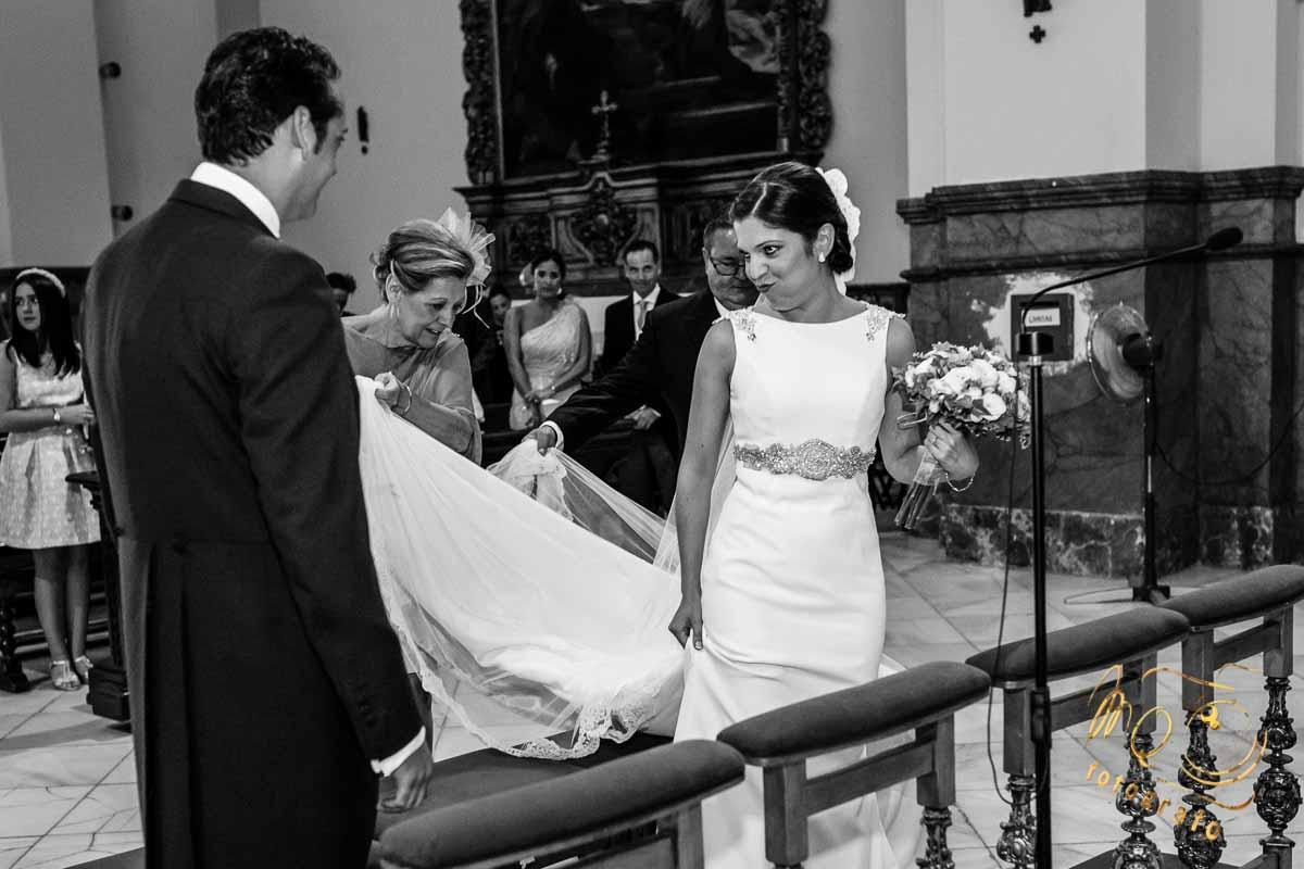 novia con mirada y gesto cómplice al encontrar al novio en el altar