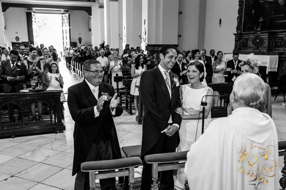pareja de novios riéndose en el altar con padrinos y sacerdote