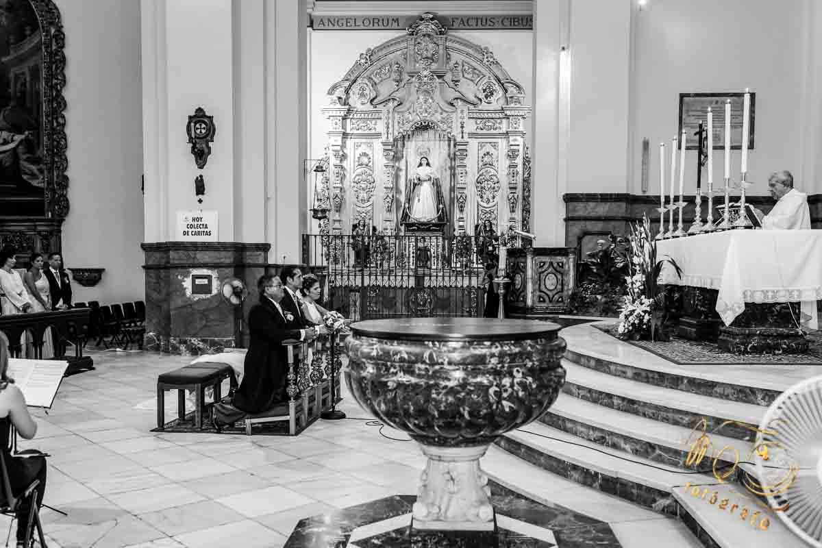 novios y padrinos en el altar de la parroquia, arrodillados