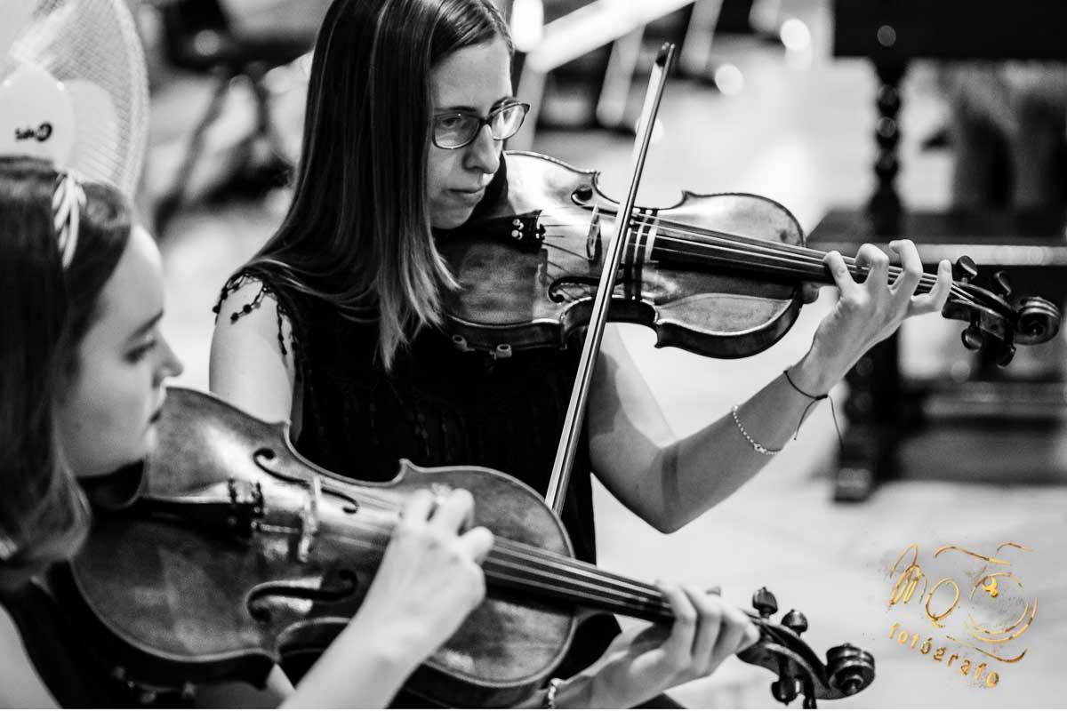 chicas tocando el violin en la iglesia