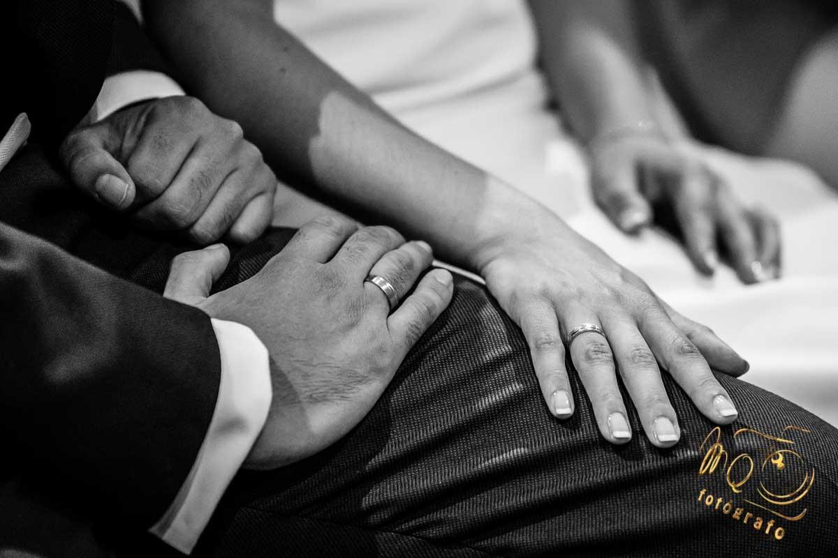 novios con sus manos juntas enseñando los anillos