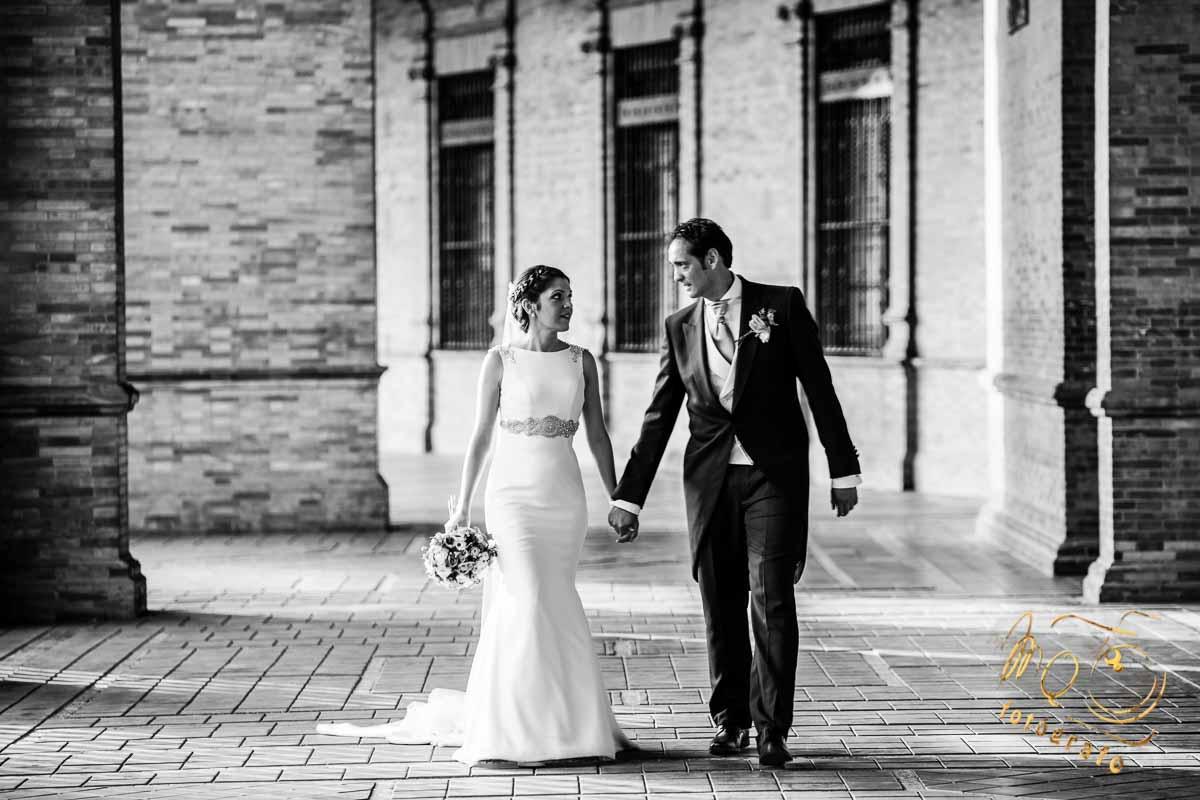 pareja de novios andando en pasillo de plaza de España Sevilla