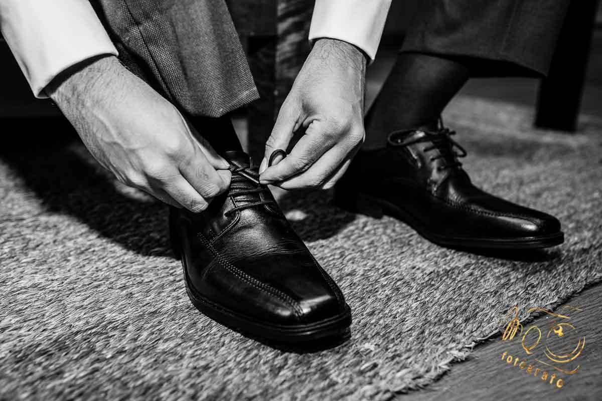 novio poniéndose los zapatos en su habitación