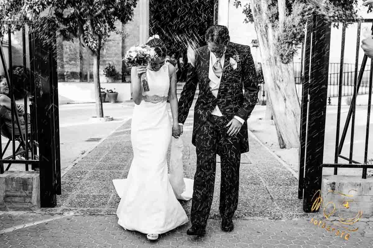 novios recien casados saliendo de la iglesia, bañados en arroz
