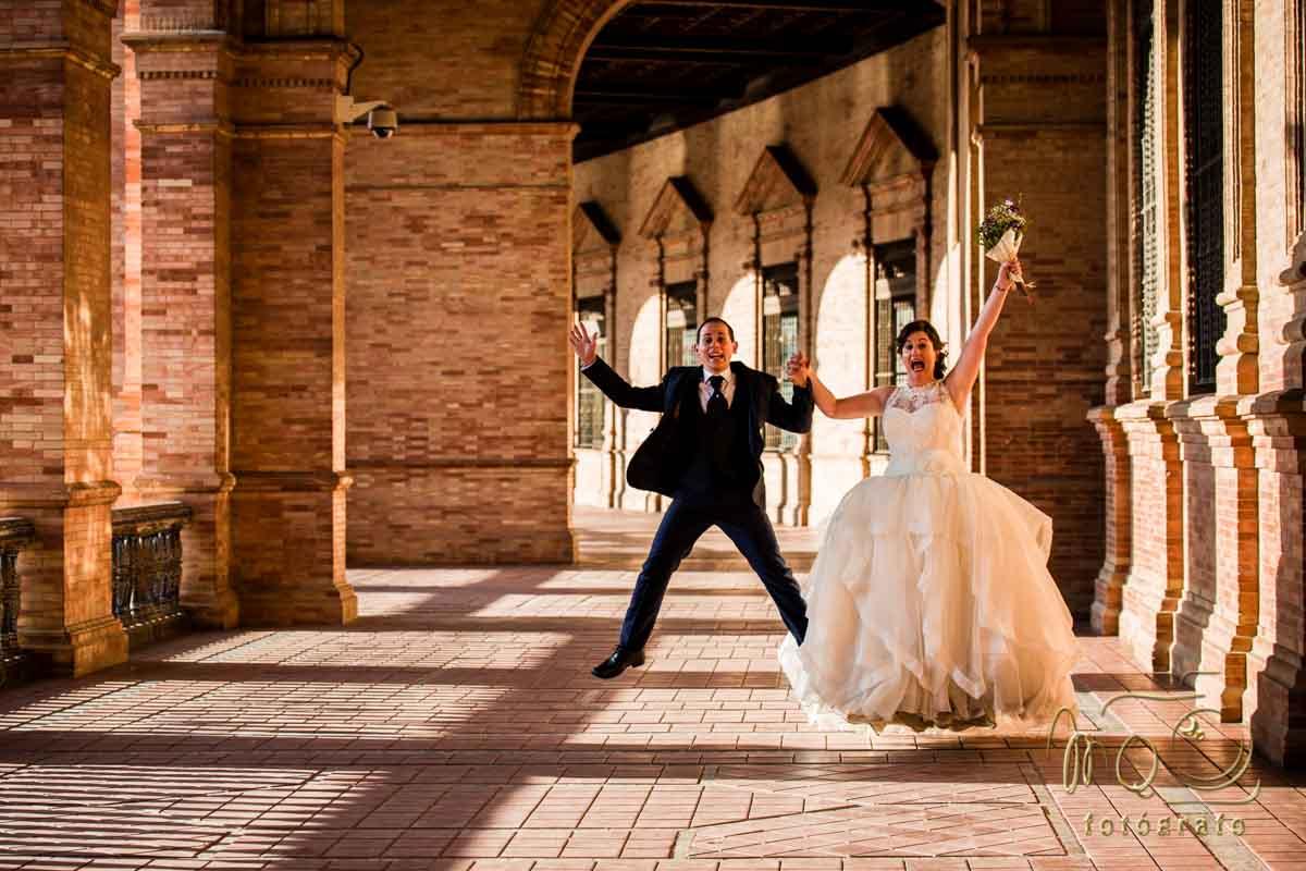 pareja de novios saltando en pasadizo de la plaza de España en Sevilla