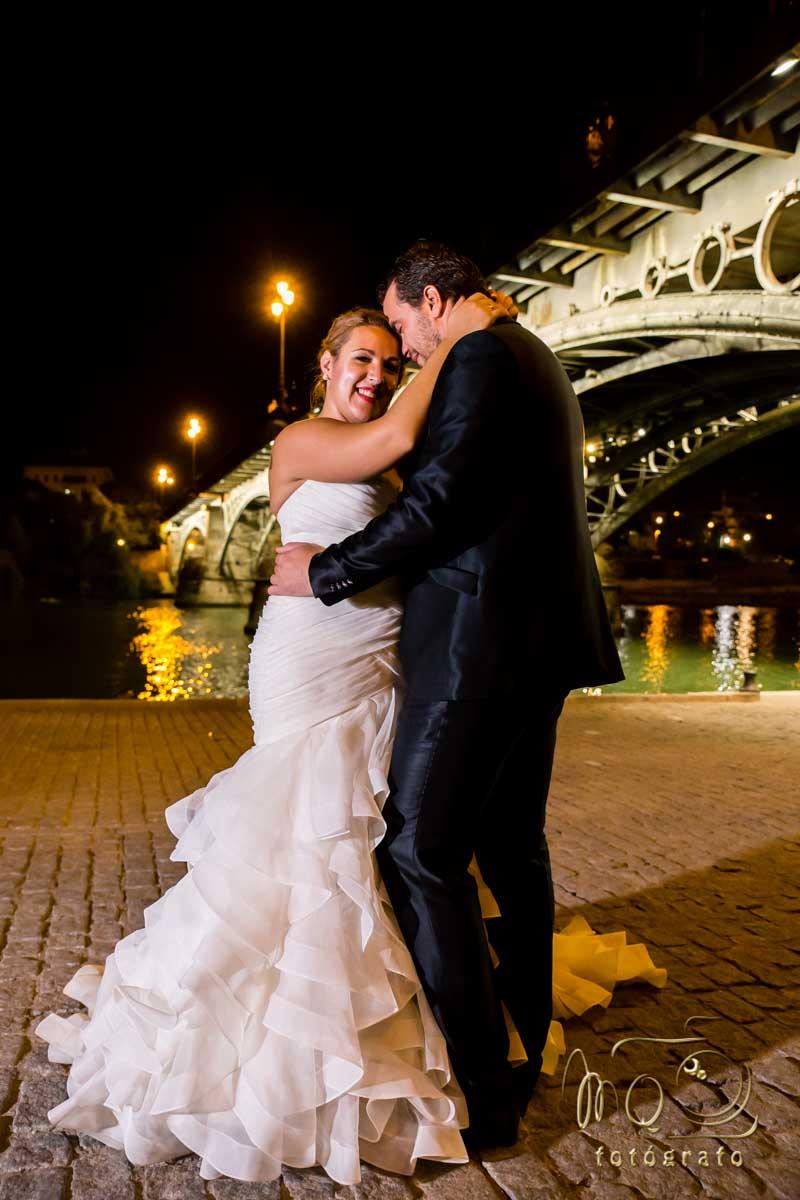 primer plano de pareja de recien casados besándose bajo puente de Triana en Sevilla de noche