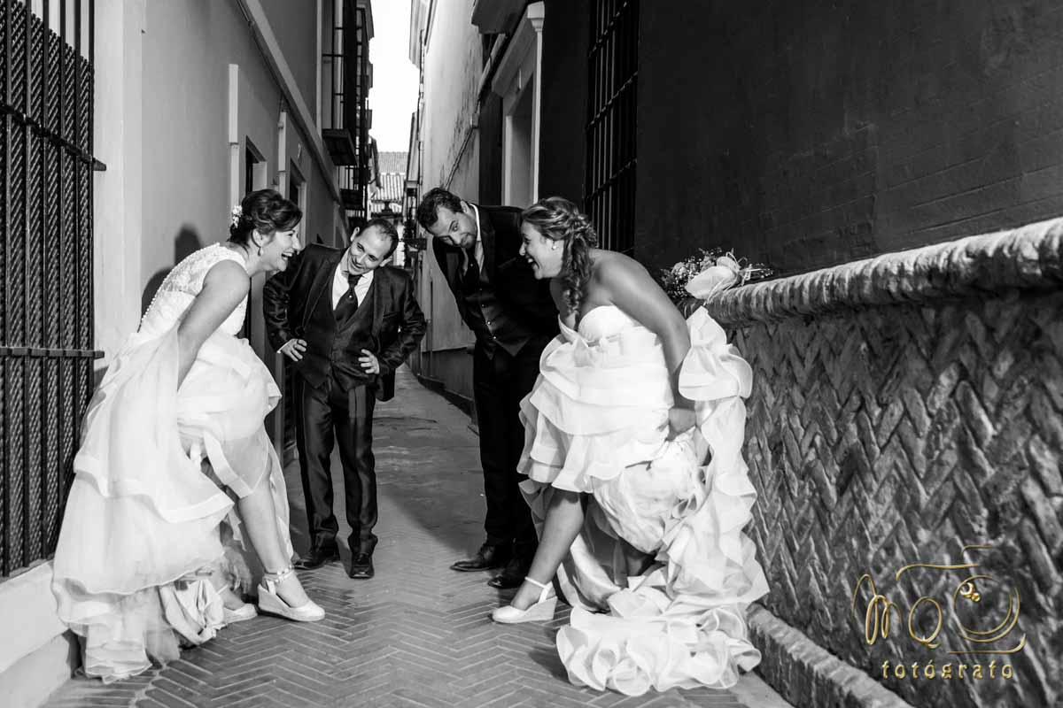 dos parejas de novios riéndose en callejón