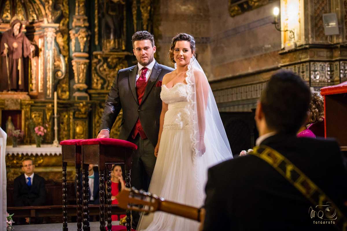 novios en el altar durante su boda mirando a cantante con guitarra
