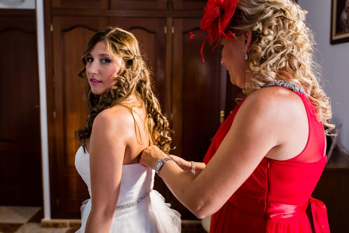 novia en su habitación con su madre abrochándole el vestido