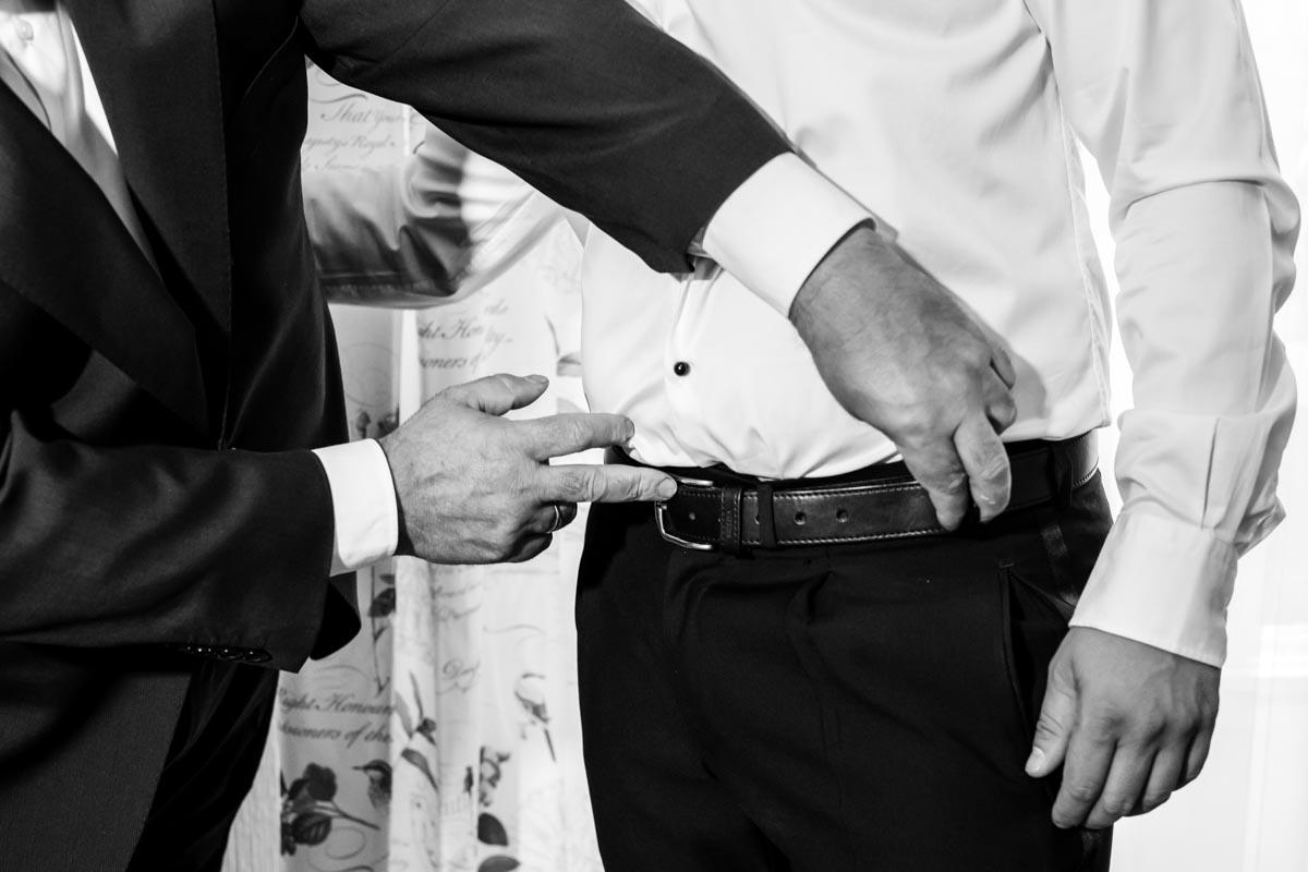 padre del novio abrochándole el cinturon