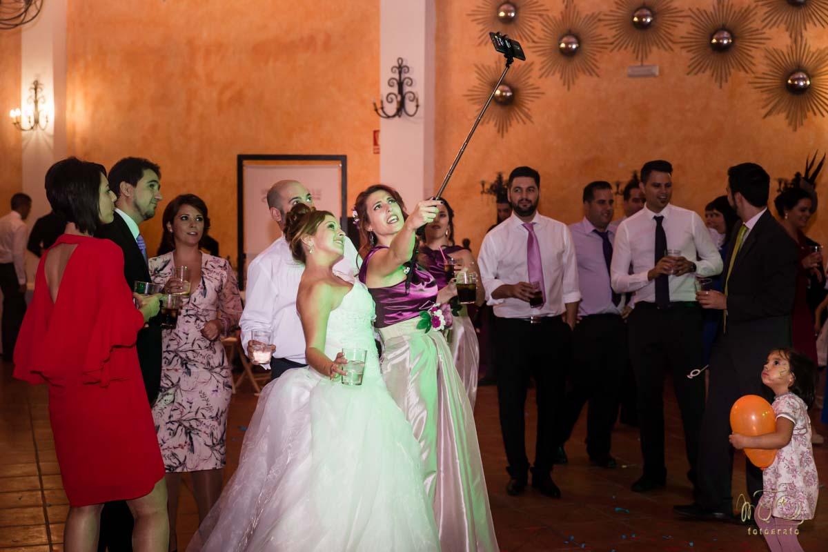 Novia en la celebración haciéndose un selfie y niña mirándola