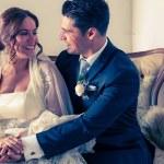 Portada del álbum de bodas pareja de recién casados sentados en un sillón mirándose