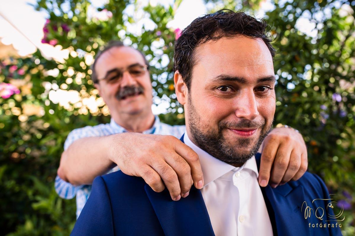 novio en primer plano con el padre a la espalda colocándole el cuello de la camisa