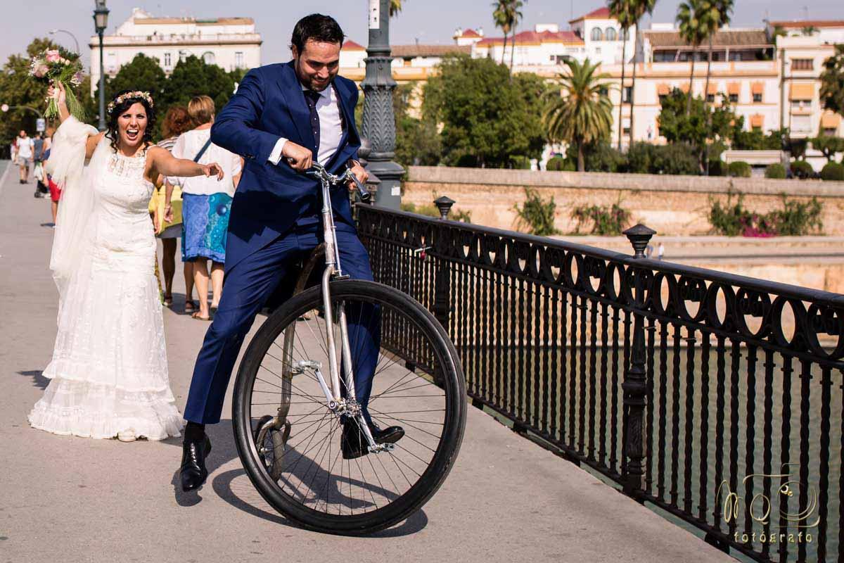 novio en bicicleta y novia tras el con ramo de flores levantado