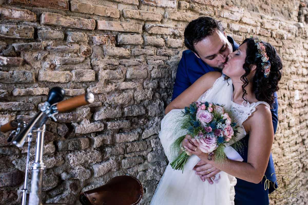 novios besándose sobre una pared de ladrillo junto a una bicicleta