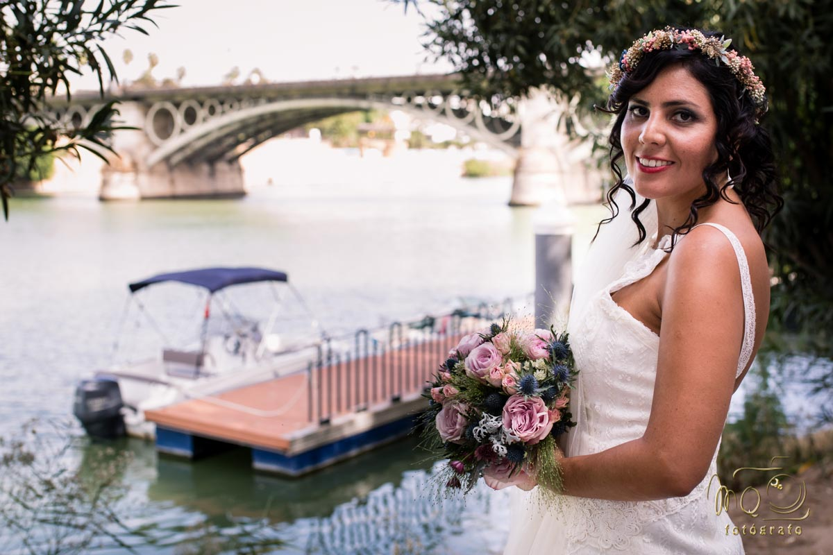 novia en la orilla del río Guadalquivir con ramo de novia en la mano