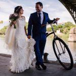 pareja de novios paseando con una bicicleta debajo de un puente