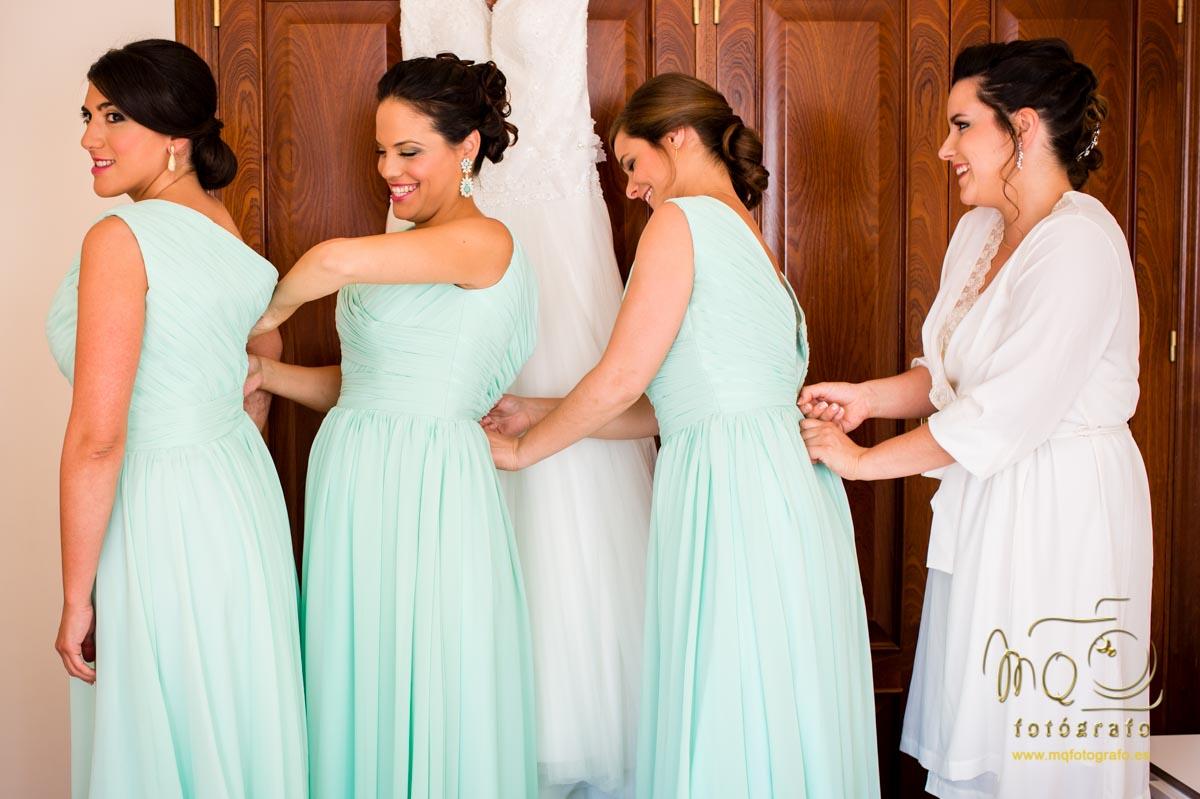 damas de honor y novia en fila, abrochándose los vestidos