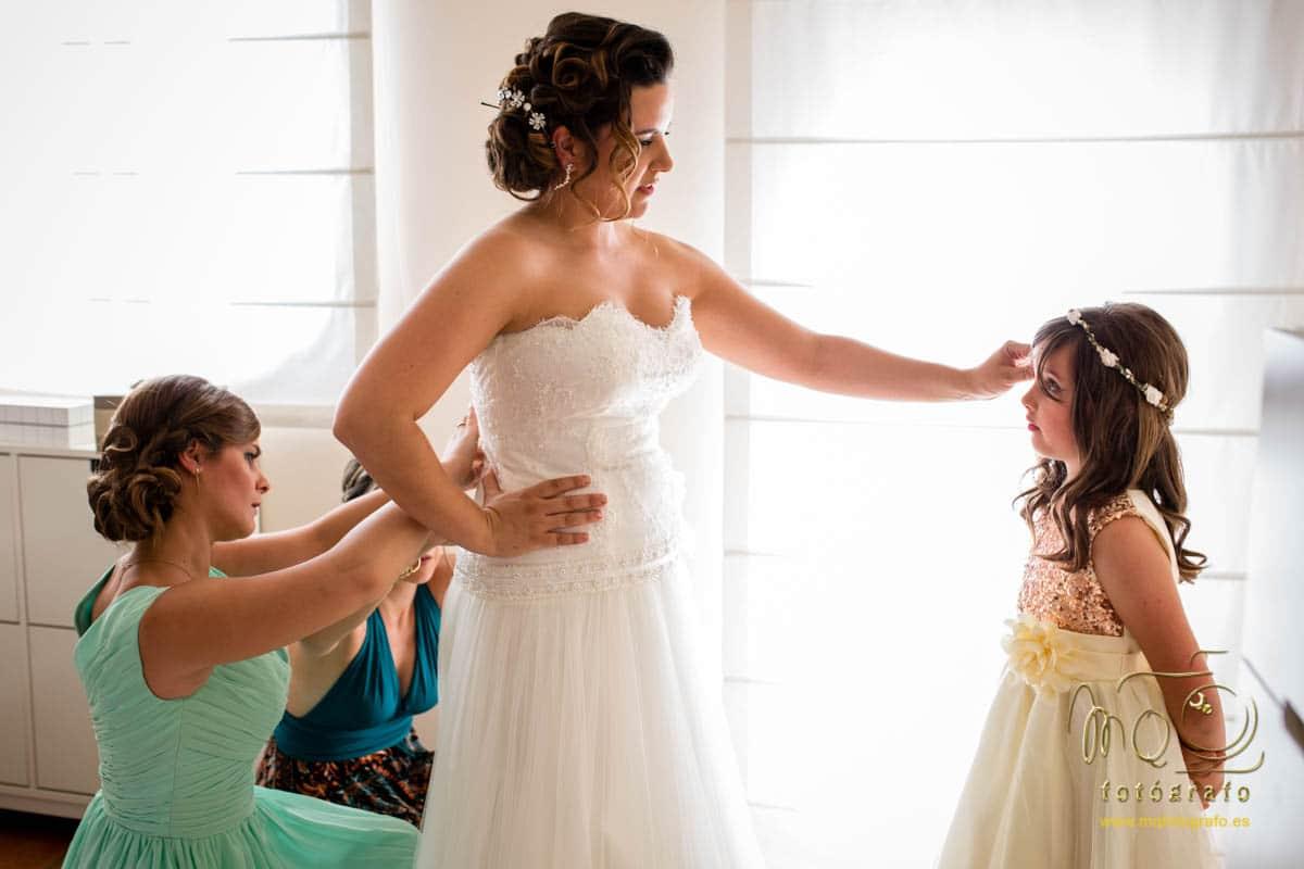 novia frente a sobrina pequeña y dama de honor abrochándo el vestido