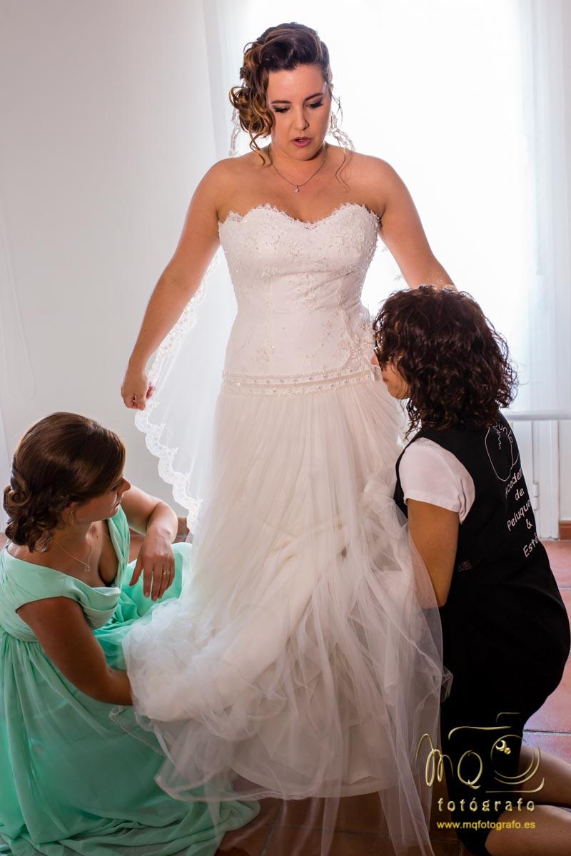 una dama de hornor y la maquilladora poniendo bien la cola del vestido de novia