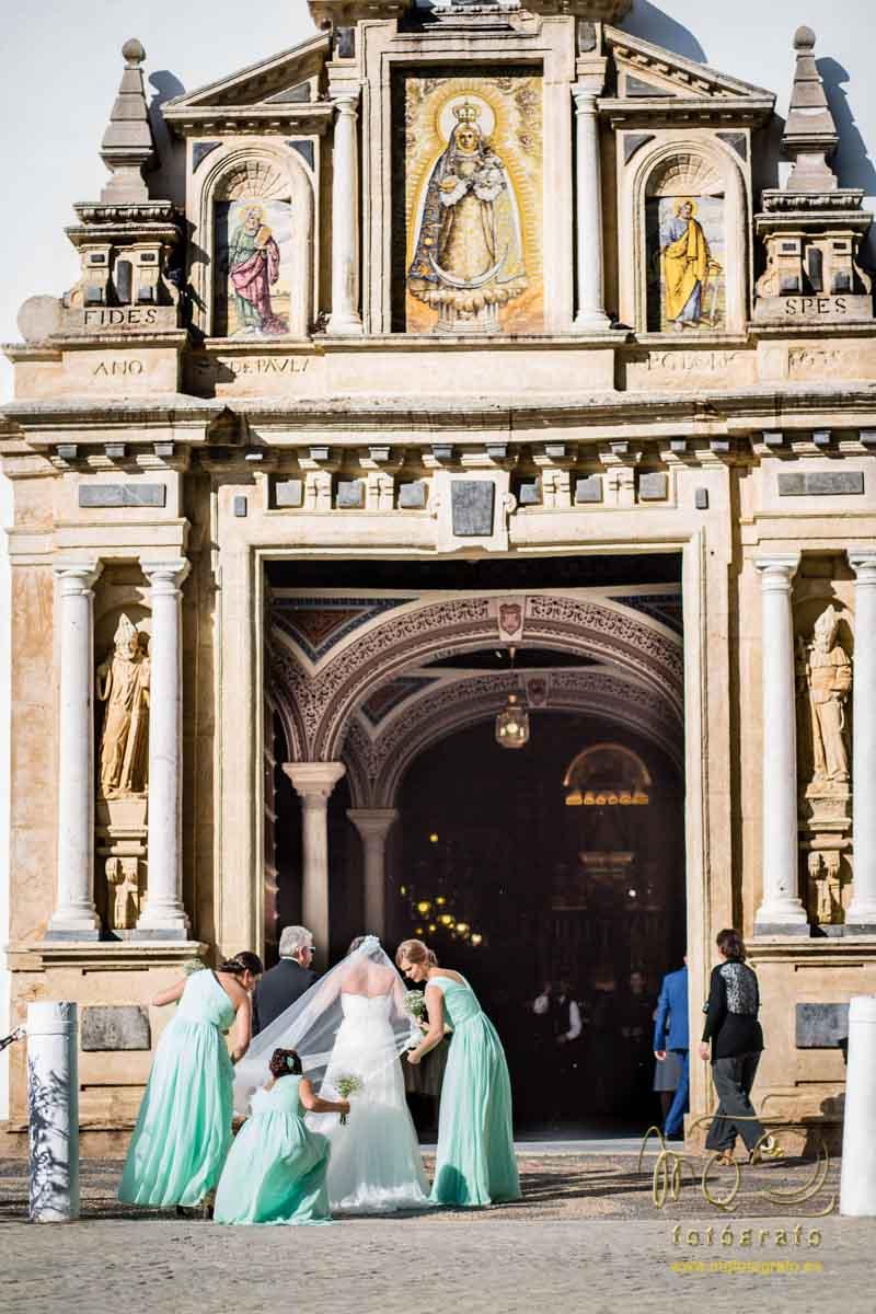 novia delante de la iglesia y las damas poniendo bien el vestido y el velo