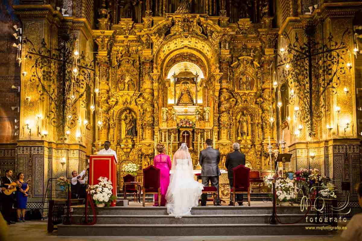novios y padrinos de pié y de espaldas en el altar
