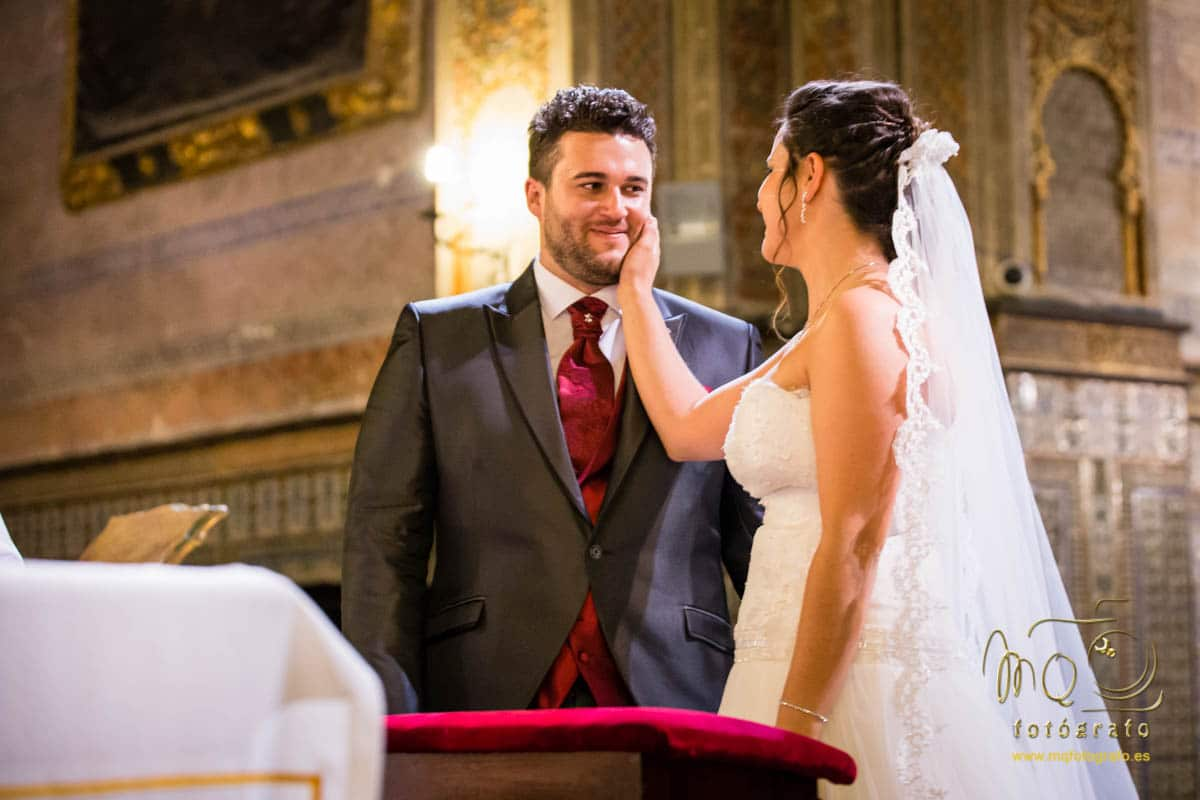 novios en el altar, la novia le pone la mano en la cara al novio