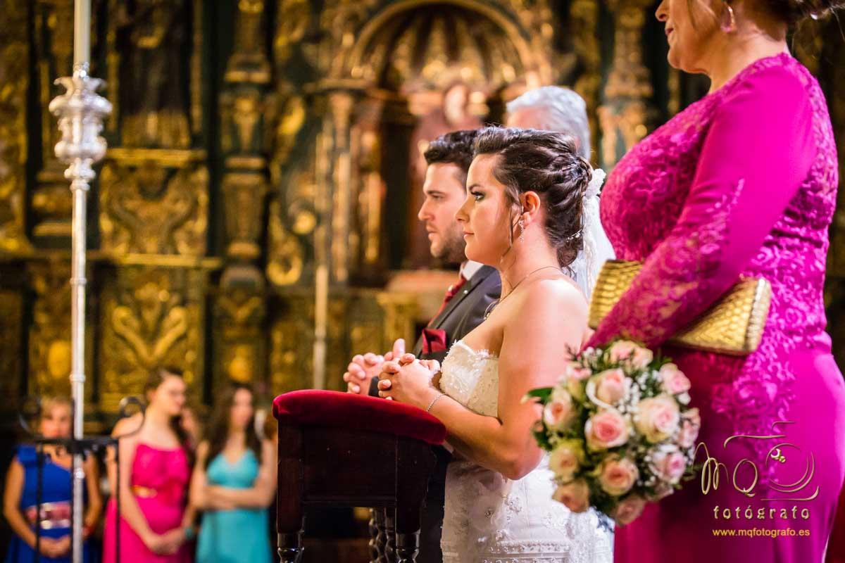 novios de perfil arrodillados en el altar