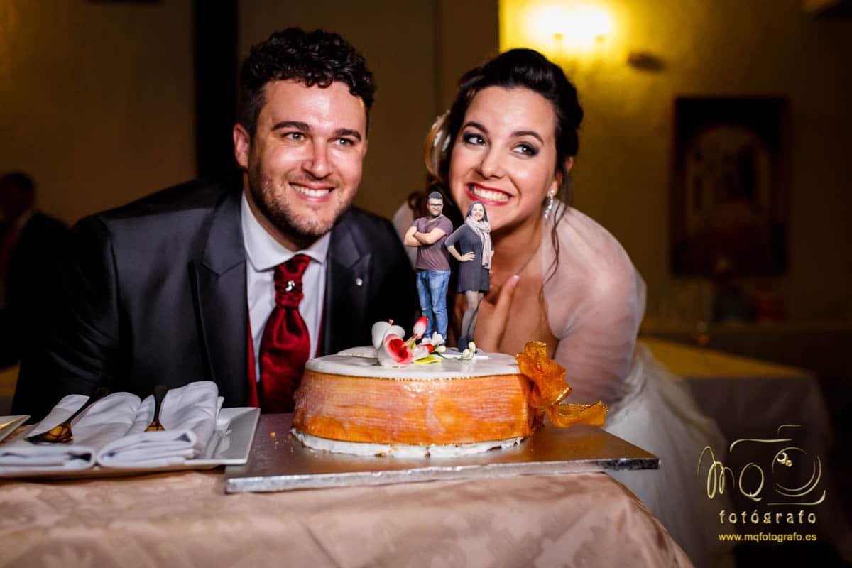 novios junto a la tarta que tiene unas figuras de ellos mismos
