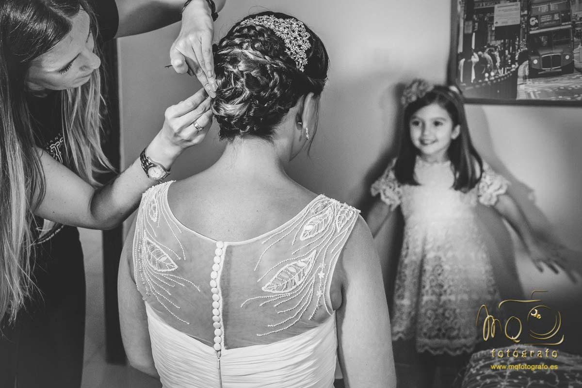 peluquera arreglando el moño de la novia y niña mirándola