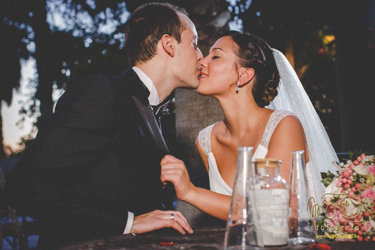 exteriores de boda novios sentados en una mesa del jardín besándose