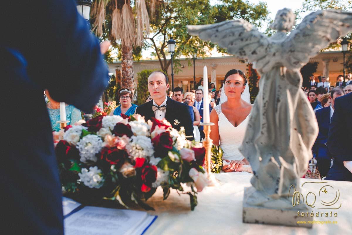 Ceremonia en el jardín de Hacienda Azahares, novios sentados mirando al altar