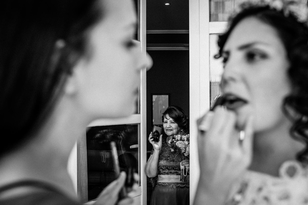 maquilladora retocando a la novia y madre de fondo