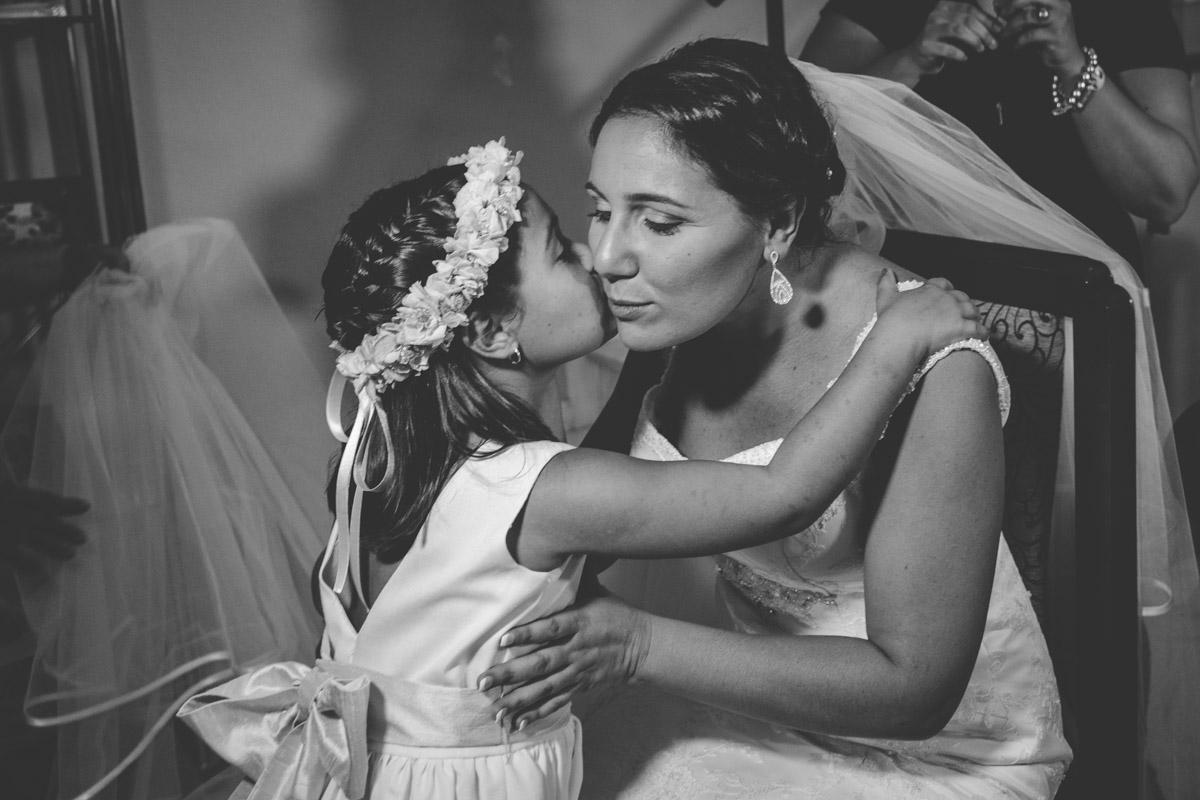 fotografía de boda, hija besando en la cara a la novia, su madre