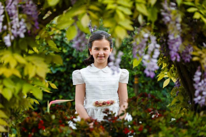 niña vestida de comunión entre las flores de un pozo