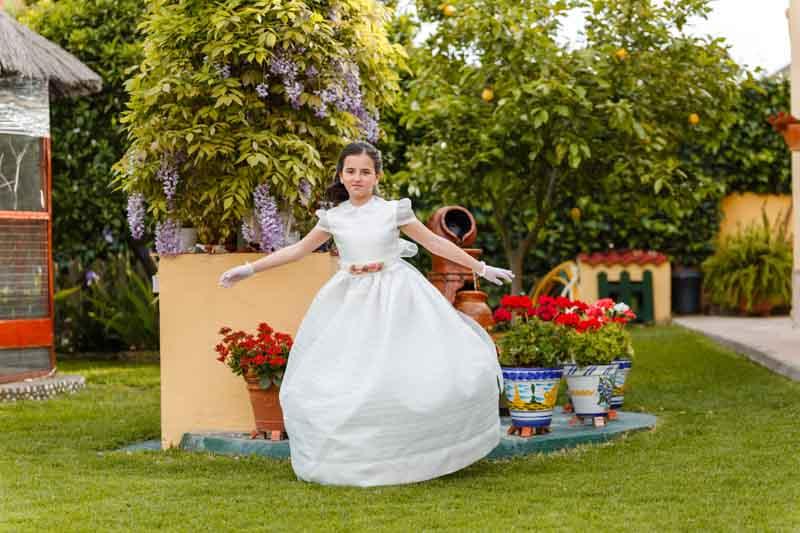 niña vestida de comunión divirtiéndose en el jardín