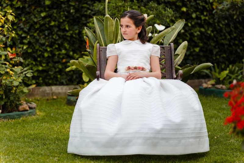 niña vestida de comunión sentada el sillón luciendo vestido