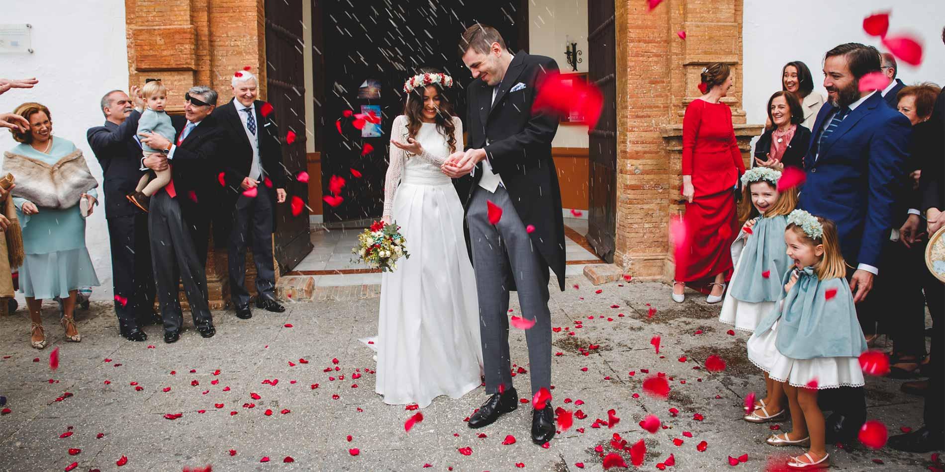 Fotografías de boda en sevilla, novios saliendo de la iglesia con lluvia de arroz y pétalos