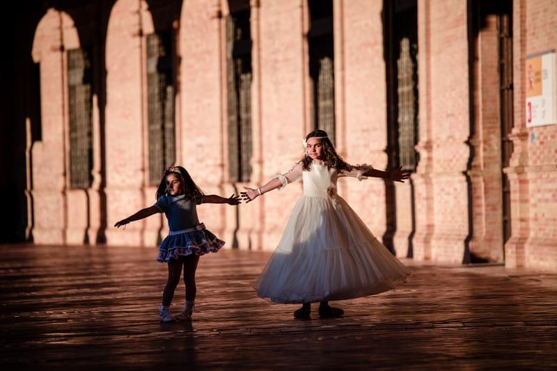 fotografía de comuniones niña vestida de comunión de brazos abiertos con su hermana en plaza de España de Sevilla