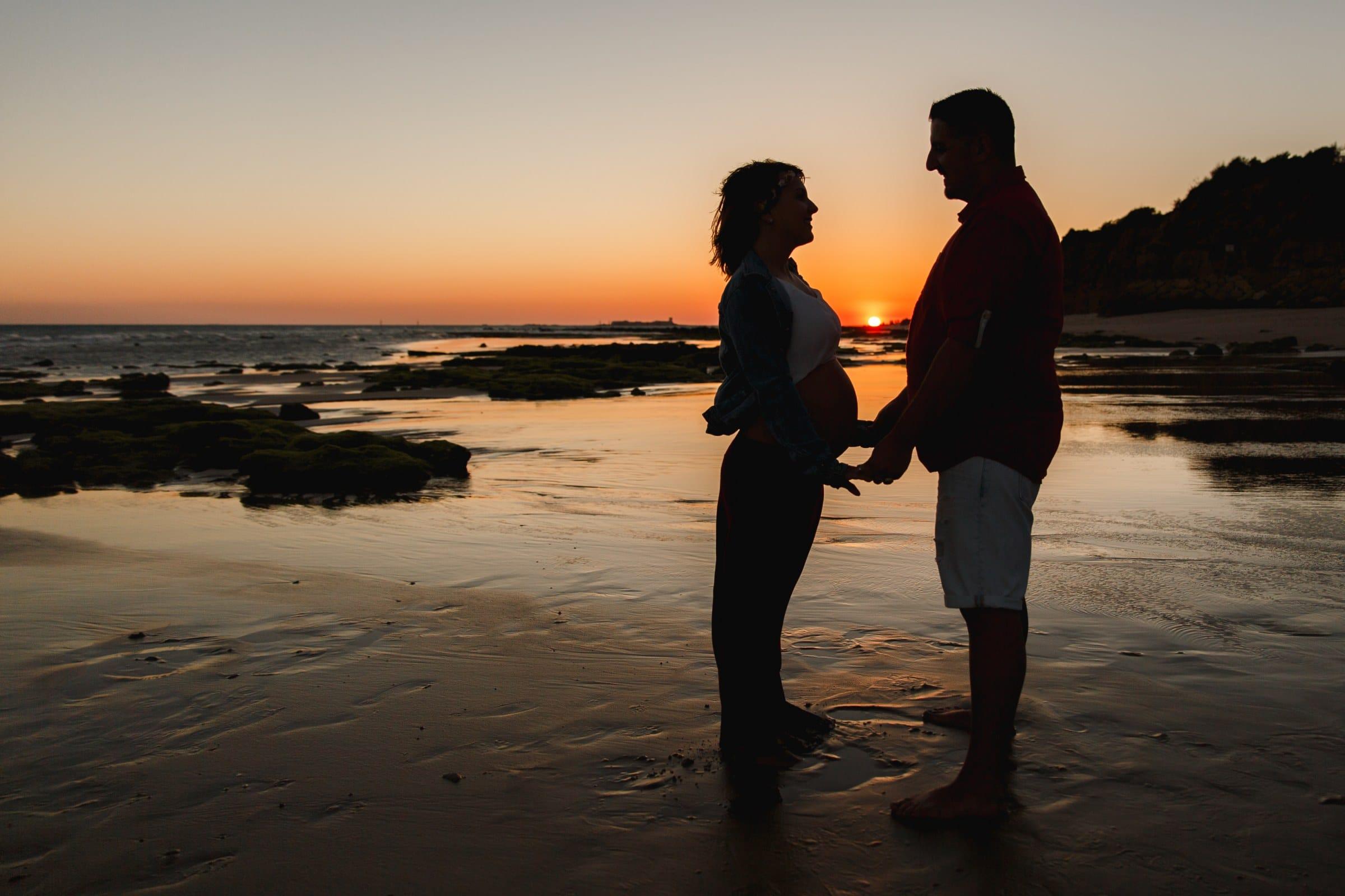 mujer embarazada y su marido en una sesión de fotos de embarazo en la playa a contraluz en el atardecer